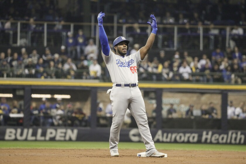 The Dodgers' Yasiel Puig celebrates hitting a second-inning double in Game 7 of the NLCS against the Milwaukee Brewers.