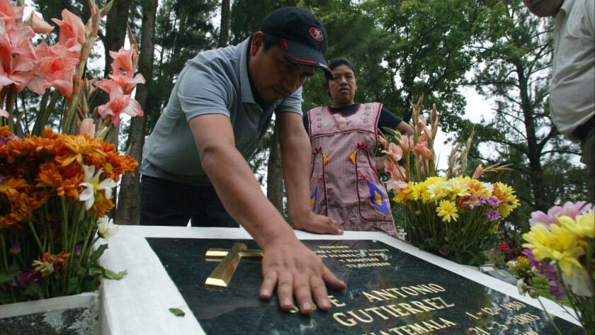 Antonio Paz lays his hand on the headstone of his brother-in-law, slain Marine Jose Antonio Gutierrez, while visiting the grave with his wife, Engracia Cirin, Gutierrez's sister.