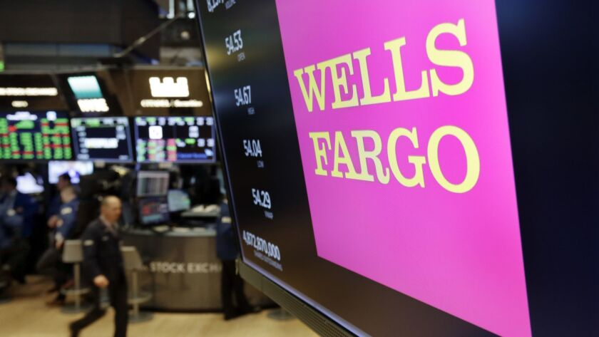 FILE- In this May 17, 2018, file photo, the logo for Wells Fargo appears above a trading post on the