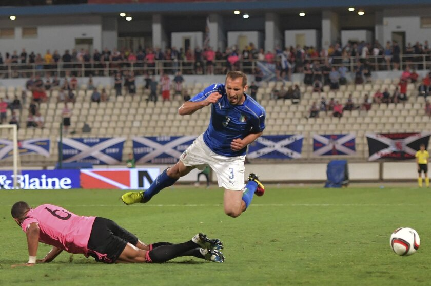 Italy's Giorgio Chiellini, right, flies over Scotland's Matt Phillips during a friendly match between Italy and Scotland, in preparation for the upcoming Euro 2016 European Championships, at the Ta' Qali stadium in Attard, Malta, Sunday, May 29, 2016. (AP Photo/Rene Rossignaud)