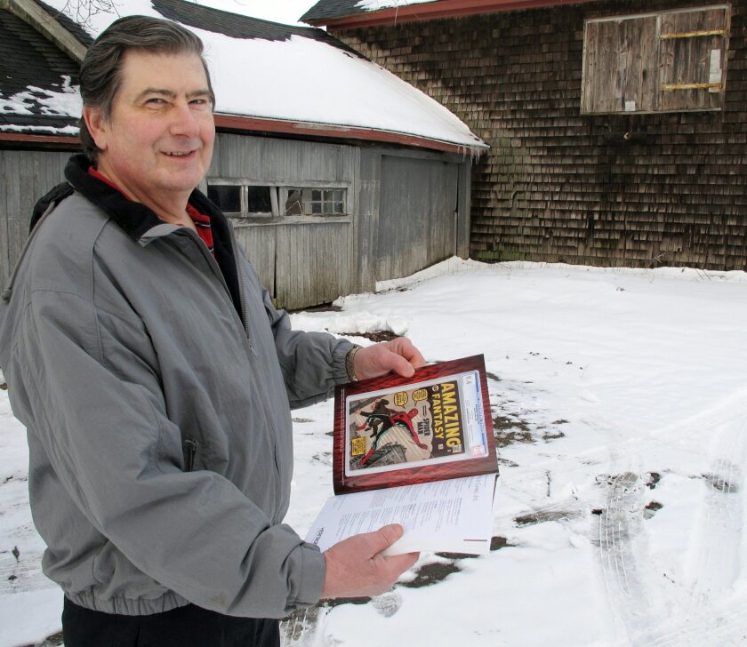 """In this photo taken Tuesday, Feb. 9, 2016, in Calverton, N.Y., Walter Yacoboski holds an auction guide featuring one of his comic books, """"Amazing Fantasy"""" No. 15, which features the Spider-Man character. Yacoboski bought the comic book as an investment in 1980 for $1,200. Some experts believe it co"""