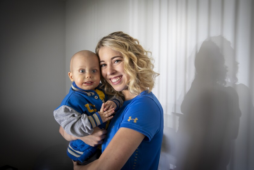 UCLA gymnast Mercedez Sanchez holds her 1-year-old brother, Liam Clark, who is battling a rare form of cancer.