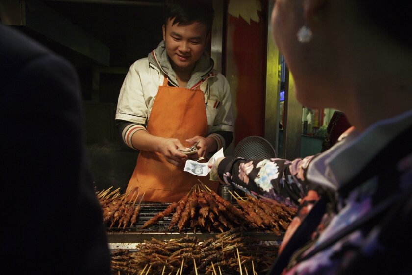 In this photo taken Thursday, Oct. 29, 2015, a street vendor collects money in Beijing, China. China announced Tuesday, Nov. 3, 2015 it will allow its tightly managed yuan to trade freely by 2020, potentially easing trade tensions with the United States and other nations. (AP Photo/Ng Han Guan)