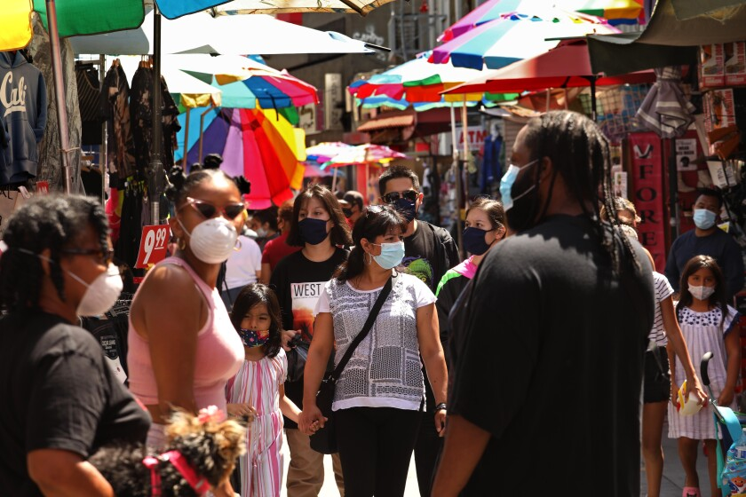 Shoppers, wearing masks to protect themselves from coronavirus, shop on Santee Alley in downtown Los Angeles.