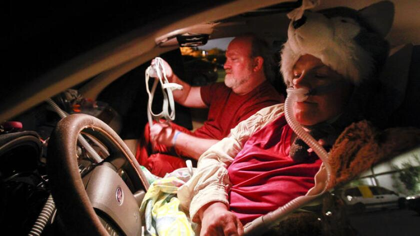 Dyana and Dale Stark use a long extension cord to plug in CPAP machines while they and Dale's mother, who is in the back seat, sleep in their car at the Jewish Family Service's Joan & Irwin Jacobs Campus in San Diego in 2017.