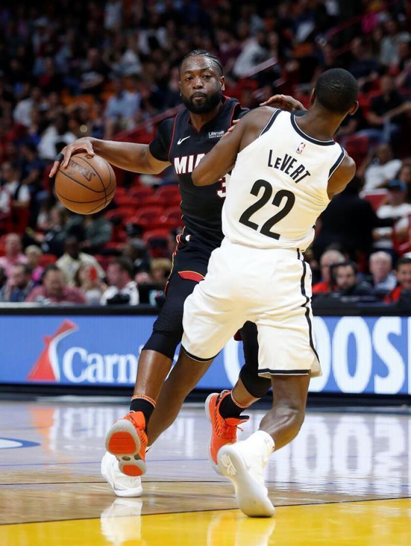 El jugador de los Miami Heat Dwyane Wade (i) es defendido por el jugador delos Nets de Brooklyn Caris LeVert (d) durante un partido de la NBA. EFE/Archivo