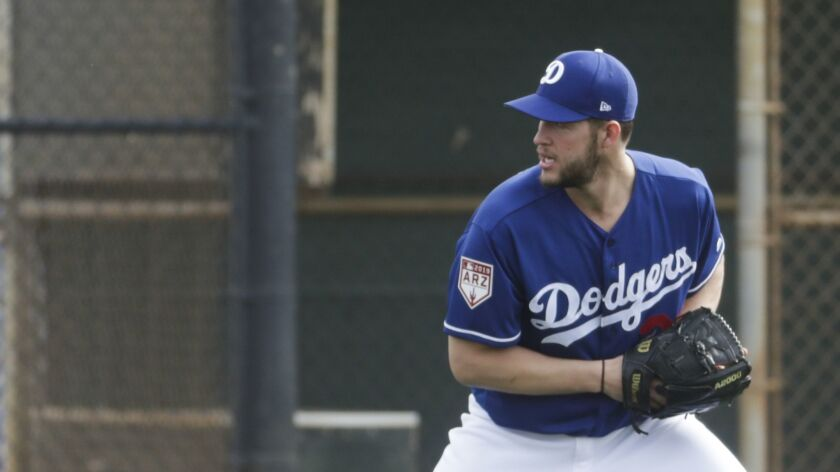Los Angeles Dodgers' Clayton Kershaw makes a play during a spring training baseball workout Wednesda
