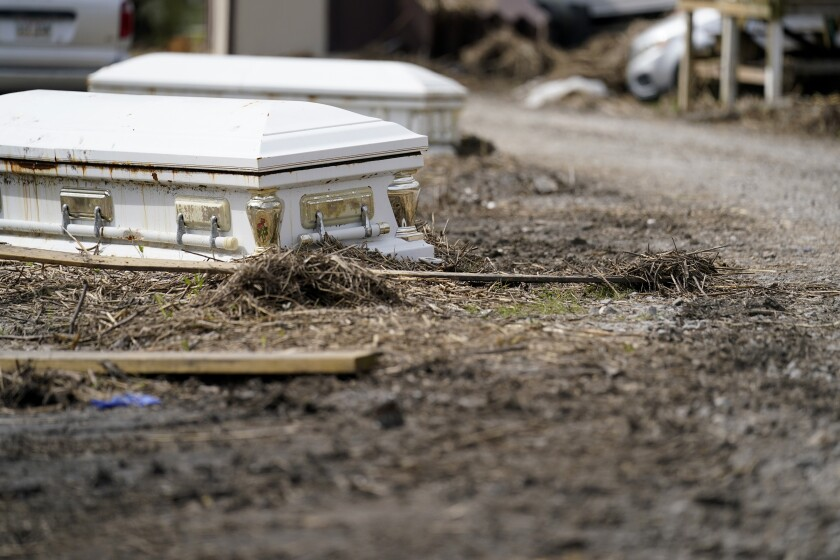 Caskets that floated from their tombs during flooding from Hurricane Ida sit along a roadside in Ironton, La., Monday, Sept. 27, 2021. Hurricane Ida swept through Louisiana with furious winds that ripped roofs off buildings and storm surge so powerful it moved homes. And what it wrought on the living it also wrought on the dead, moving vaults and caskets and adding another layer of trauma on families and communities recovering from the powerful storm. (AP Photo/Gerald Herbert)