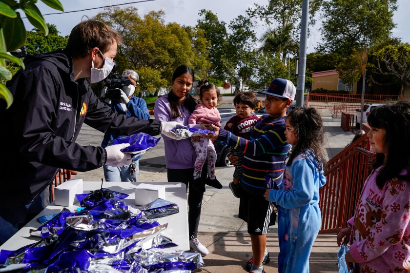 Los Angeles Unified School District board member Nick Melvoin hands headphones to students at the Mar Vista Family Center on Wednesday.