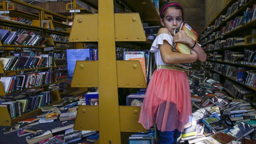 Zoe Pineda, 7, helps clean up the Ridgecrest Branch Library damaged by the Southern California earthquake.