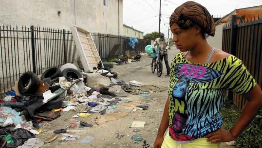 Dava Florence observa la basura acumulada en un callejón que se encuentra detrás de su casa en East 107th Street en Los Angeles.