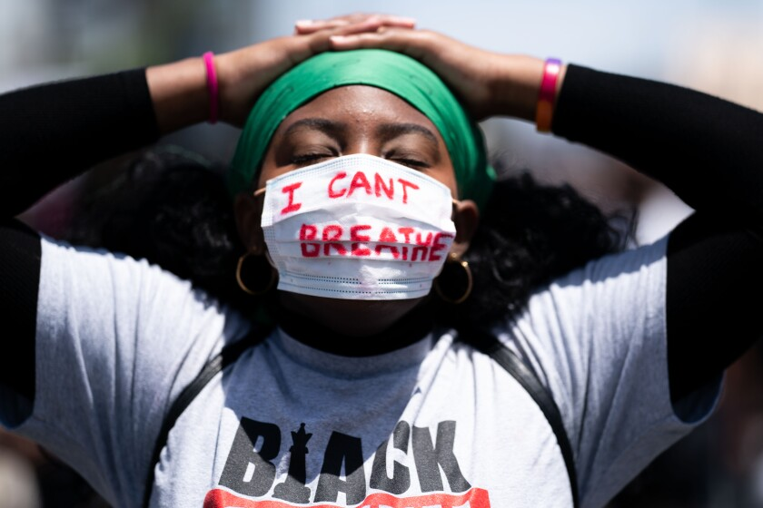 "A protester wears a face mask with the words ""I can't breathe."""