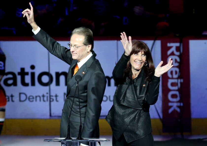 Ducks owners Henry and Susan Samueli acknowledge the crowd during Teemu Selanne's jersey retirement ceremony at Honda Center in January 2015.