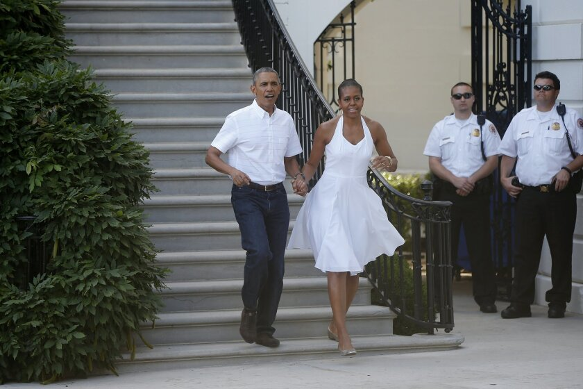 President Barack Obama and first lady Michelle Obama walk from the South Portico to greet military families as they host an Independence Day celebration on the South Lawn at the White House in Washington, Friday, July 4, 2014. (AP Photo/Charles Dharapak)