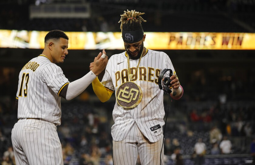 San Diego Padres' Fernando Tatis Jr. gets the swag chain from Manny Machado after a win against the New York Mets at Petco Park on Thursday, June 3, 2021.