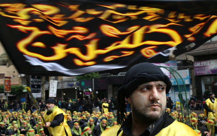 A Lebanese Shiite supporter of Hezbollah, right, with mud on his face brought from Karbala, according worshippers, listens to the story of Imam Hussein, as other man, left background, wave a religious flags during the holy day of Ashoura, in the southern suburb of Beirut, Lebanon, Tuesday Nov. 4, 2