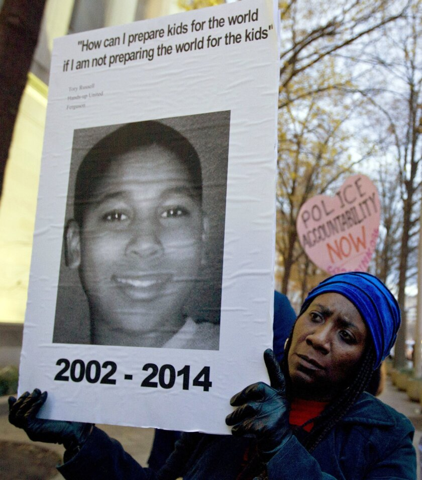 FILE - In this Dec. 1, 2014 file photo, Tomiko Shine holds up a picture of Tamir Rice, the 12 year old boy fatally shot by a rookie police officer in Cleveland, Ohio, on Nov. 22, during a protest in Washington, D.C. The city of Cleveland requested Rice's estate to pay $500 for his ambulance ride an