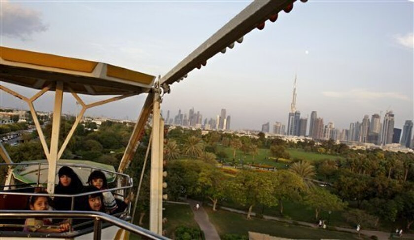 The Dubai skyline is seen in the background as children ride on a Ferris wheel at the Safa park in Dubai, United Arab Emirates, Monday, Nov. 30, 2009. (AP Photo/Kamran Jebreili)