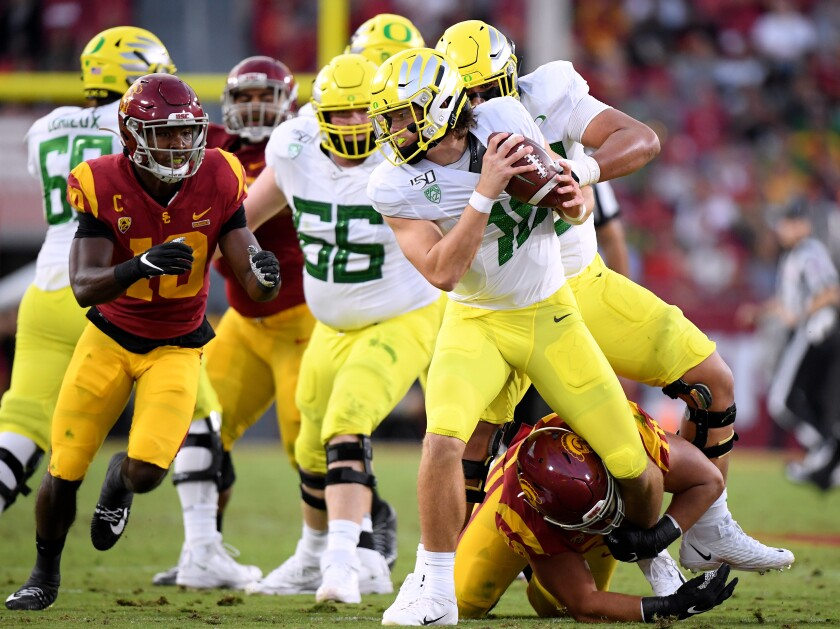USC's Jay Tufele has a hold on Oregon's Justin Herbert on Nov. 2 at the Coliseum.