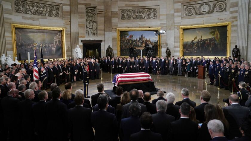 The flag-draped casket of former President George H.W. Bush lies in state in the Capitol Rotunda in