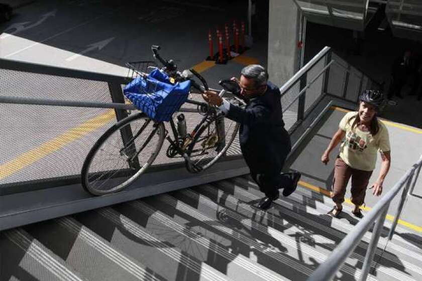Roland Cordero, director of facilities at Foothill Transit, shows Alice Strong how to use the bike rail to ascend the stairs at the El Monte bus station. Millennials prefer close-in living that is more conducive to using bikes for transportation over long car commutes, which has serious implications for future transportation funding, a new report says.