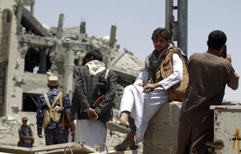 Houthi rebels look at the damage in the yard of the residence of their military commander after an airstrike destroyed the property in the Yemeni capital, Sana, on April 28.