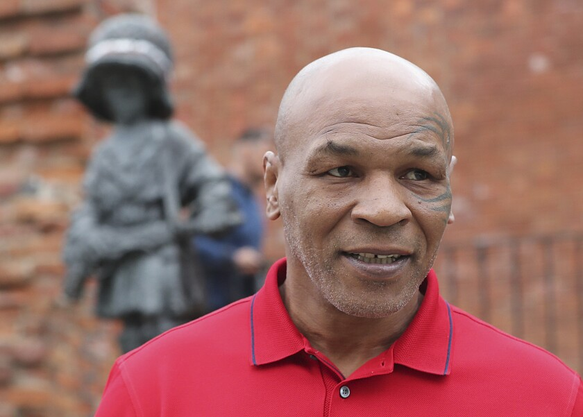 Mike Tyson, an American former heavyweight boxing champion, stands in front of a memorial to Polish suffering during World War II, during a visit to Warsaw, Poland, on Thursday June 27, 2019. (AP Photo/Czarek Sokolowski)