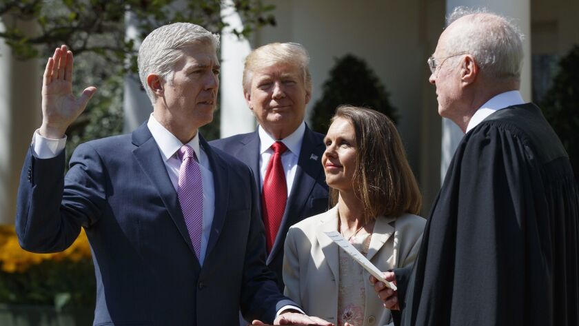 Supreme Court Justice Anthony M. Kennedy, right, administers the judicial oath to Justice Neil M. Gorsuch, who was accompanied by his wife, Marie Louise, at the White House in 2017.
