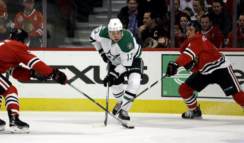 Dallas Stars center Mattias Janmark, center, battles for the puck against Chicago Blackhawks center Phillip Danault, left, and defenseman Niklas Hjalmarsson during the first period of an NHL hockey game Thursday, Feb. 11, 2016, in Chicago. (AP Photo/Nam Y. Huh)