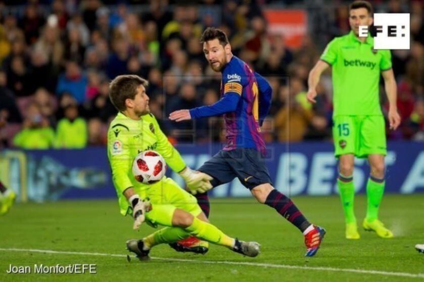 El delantero argentino del FC Barcelona, Leo Messi (c), golpea el balón ante el guardameta del Levante, Aitor Fernández (i), consiguiendo el tercer gol del equipo blaugrana durante el encuentro correspondiente a la vuelta de los octavos de final de la Copa del Rey que han disputado esta noche en el estadio Camp Nou, en Barcelona. EFE/Joan Monfort.