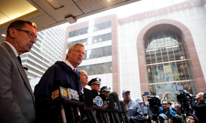 El alcalde de Nueva York, Bill de Blasio (c), el comisionado de Bomberos, Daniel Nigro (i), y el comisionado de Policía, James O'Neill (d), hablan a los medios de comunicación sobre un helicóptero que se estrelló contra el Edificio Equitable (fondo) este lunes, en el centro de Manhattan, Nueva York, (EE.UU.). EFE