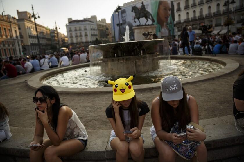 """Fans españolas juegan """"Pokémon Go"""" en el centro de Madrid, España, en una fotografía del 28 de julio de 2016. Los creadores de """"Pokémon Go"""" dijeron a The Associated Press que están implementando actualizaciones al juego para que sea respetuoso con el mundo real. (Foto AP/Daniel Ochoa de Olza)"""