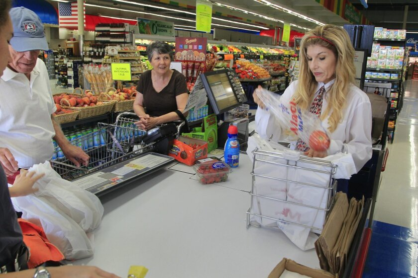 Customers checkout at Major Market in Escondido. Disposable lastic grocery bags are still available to customers in California, but a statewide ban will eliminate them starting next July.