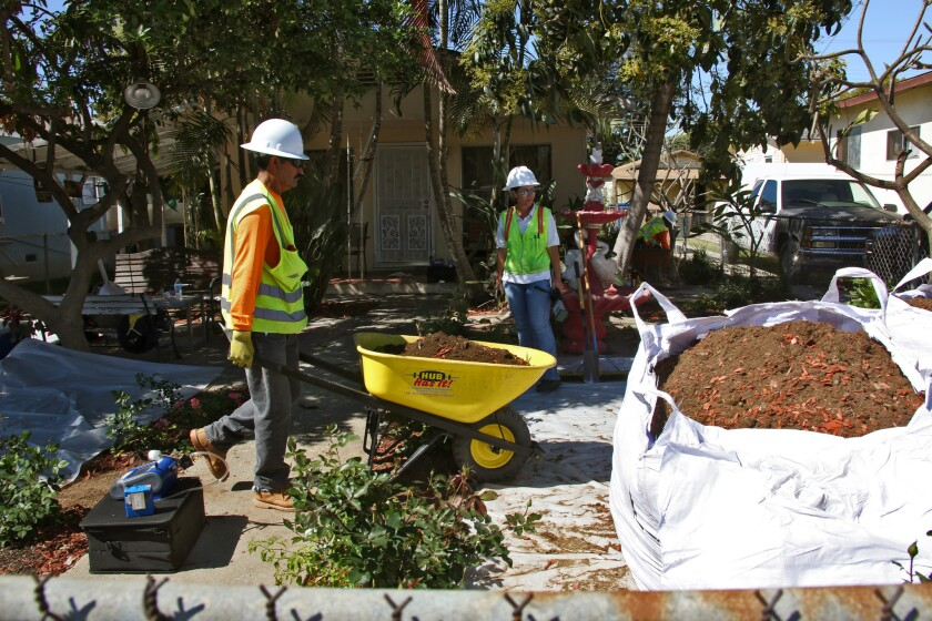 Workers remove topsoil in March from homes in Boyle Heights that may have been contaminated by lead that possibly came from Exide Technologies, a battery recycling plant in Vernon.