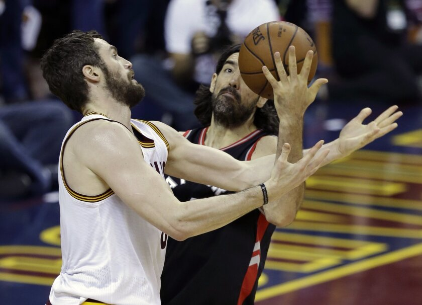 Cleveland Cavaliers' Kevin Love, left, and Toronto Raptors' Luis Scola vie for a loose ball during the first half of Game 5 of the NBA basketball Eastern Conference finals Wednesday, May 25, 2016, in Cleveland. (AP Photo/Tony Dejak)