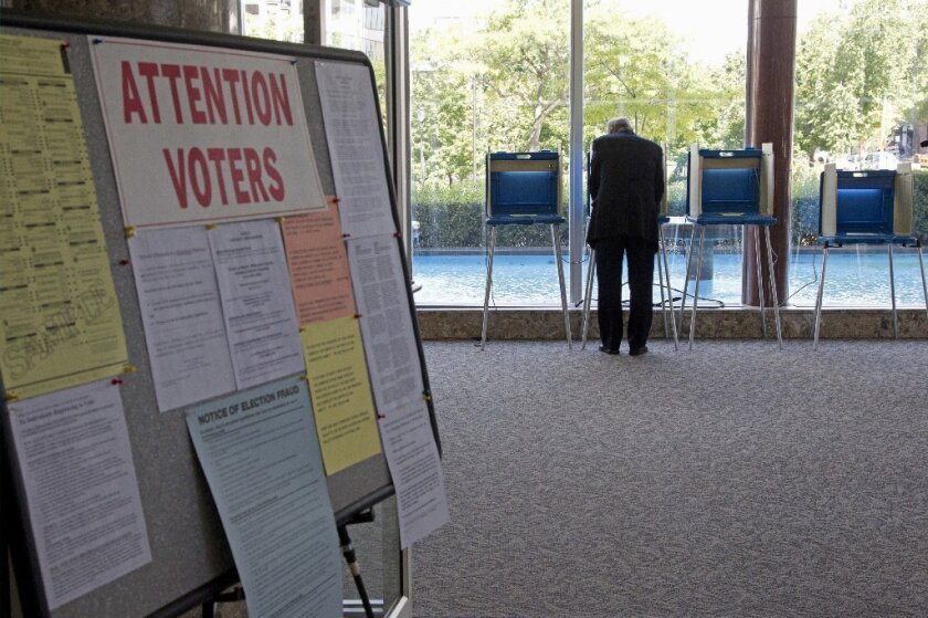 A lone voter takes part in early voting in Milwaukee. In October, the U.S. Supreme Court blocked Wisconsin's voter ID law.