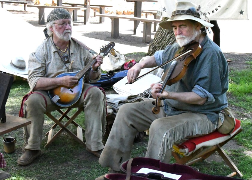 """Chuck """"Strummer"""" Preble and Larry """"Friar"""" Edwards play music from the 1880s during the 2019 Rendezvous in Old Poway Park."""