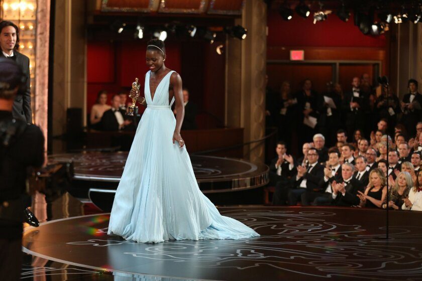 """Lupita Nyong'o accepts the award for best actress in a supporting role for """"12 Years a Slave"""" during the Oscars at the Dolby Theatre on Sunday, March 2, 2014, in Los Angeles.  (Photo by Matt Sayles/Invision/AP)"""