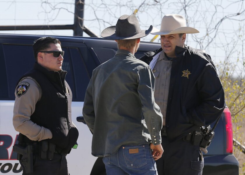 In this Saturday, Feb. 6, 2016 photo, Uvalde County Sheriffs Deputies talk with an individual while guarding the intersection to a neighborhood several miles outside of Uvalde after a standoff resulted in multiple deaths. The incident started on Friday.  (Kin Man Hui, San Antonio Express-News via A