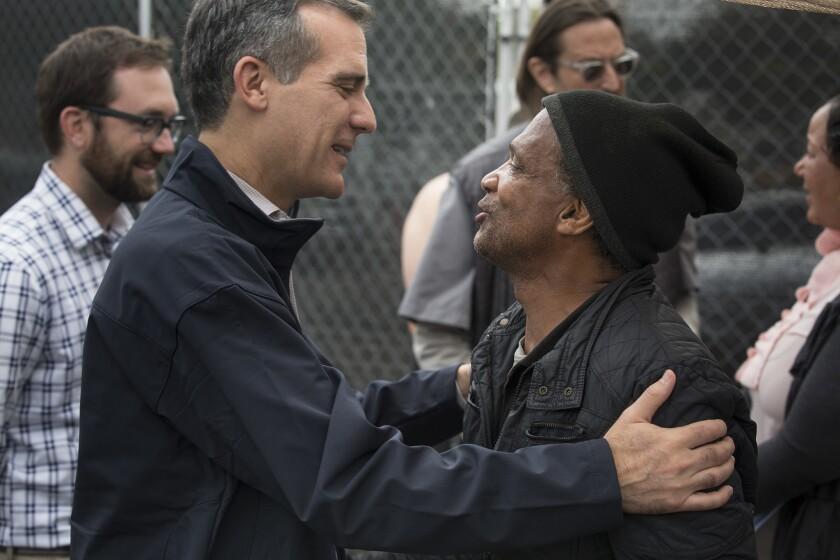 El alcalde de Los Ángeles, Eric Garcetti (izquierda) abraza Anthony Hereford, de 58 años de edad, en Hollywood durante una reunión con personas desamparadas.