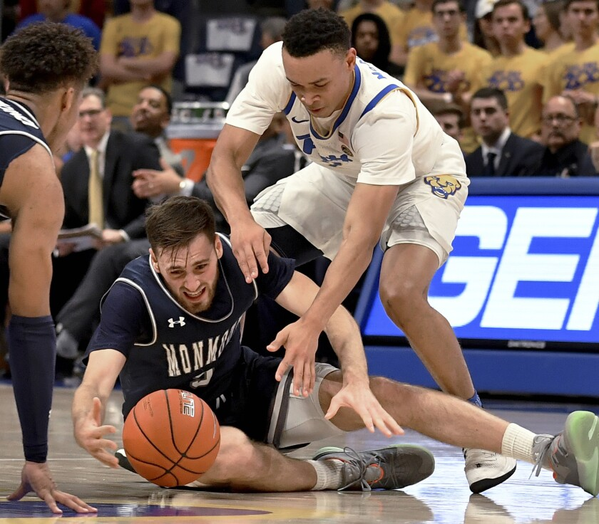 Monmouth guard George Papas reaches for a loose ball in front of Pitt guard Trey McGowens in the first half of an NCAA college basketball game Monday, Nov. 18, 2019, in Pittsburgh, Pa. (Matt Freed/Pittsburgh Post-Gazette via AP)