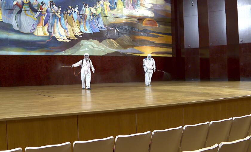 In this image made from video, a group of workers in hazmat suits disinfect stage inside the National Concert Hall in Taipei, Friday, March 6, 2020. Taiwan's National Concert Hall cancels performance for disinfectant on Friday after an Australian composer who had visited was confirmed with coronavirus. (FTV via AP)