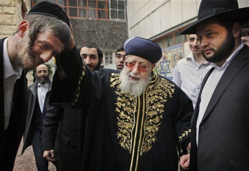 FILE - In this Feb. 10, 2009 file photo, Rabbi Ovadia Yosef, center, Jewish spiritual leader of Israel's Shas party, blesses a man after casting his ballot at a polling station in Jerusalem. An Israeli health official said Saturday, Jan. 12, 2013, that influential Yosef has been hospitalized after feeling unwell. (AP Photo/Kevin Frayer, File)