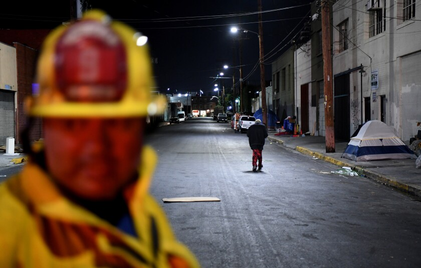 Station No. 9 firefighter Tony Navarro looks on as a homeless woman walks by during a training session