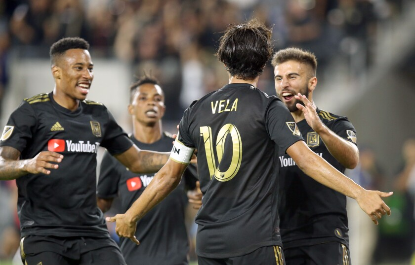 LAFC's Carlos Vela celebrates with teammates after scoring during the second half of a 3-3 tie against the Galaxy on Sunday.