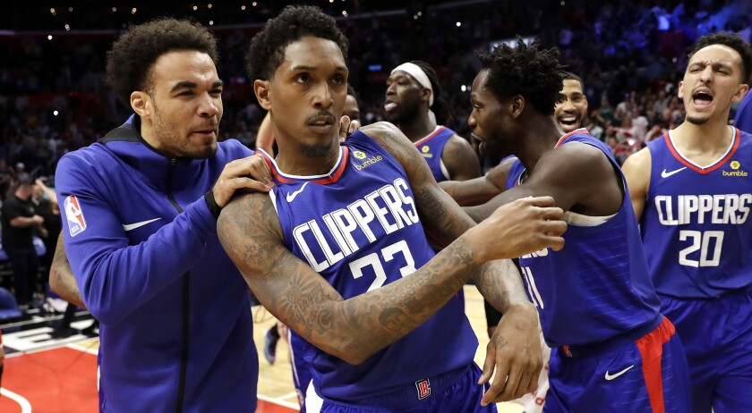 Clippers guard Lou Williams (23) is mobbed by teammates after making the game-winning shot against the Nets on Sunday.