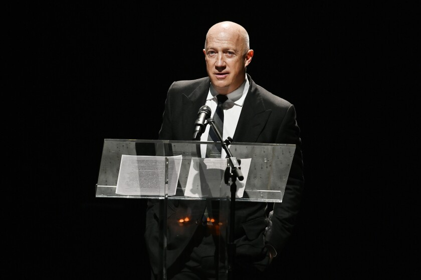 A man in a suit and tie speaks at a lectern on a dark stage