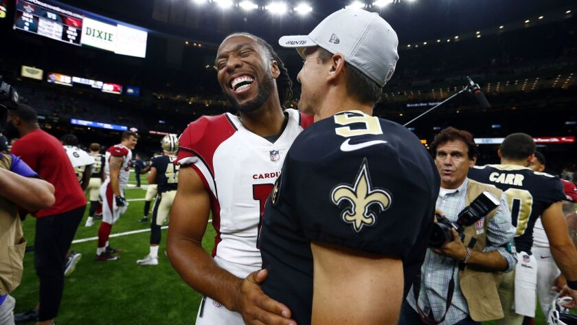 Arizona Cardinals wide receiver Larry Fitzgerald laughs with New Orleans Saints quarterback Drew Bre