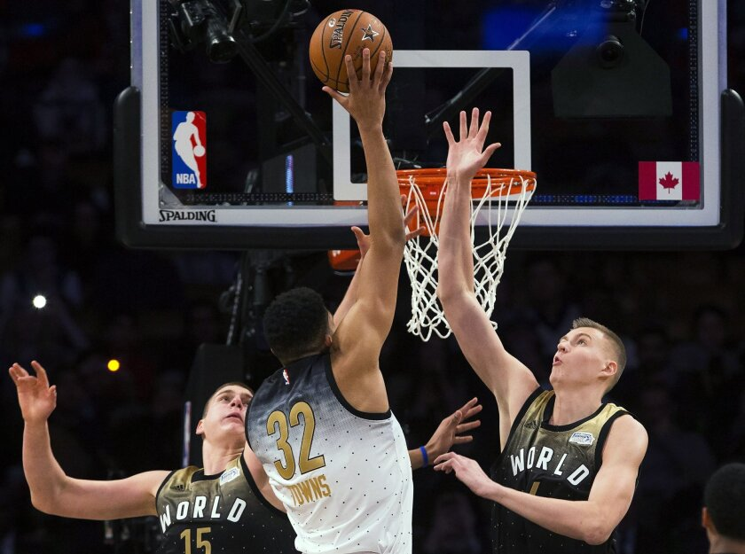 U.S. forward Karl-Anthony Towns (32) drives to the net past World's Nikola Jokic (15) and Kristaps Porzingis (6) during the first half of the NBA Rising Stars Challenge basketball game in Toronto on Friday, Feb. 12, 2016. (Mark Blinch/The Canadian Press via AP)