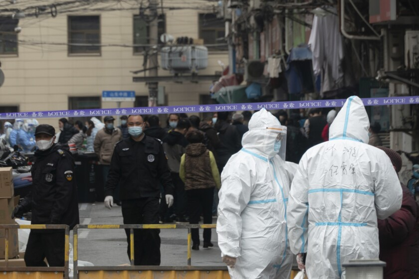 Police officers and workers in protective suits close off a neighborhood as it is placed under lockdown in Shanghai, China, Thursday, Jan. 21, 2021. Shanghai has imposed lockdowns on two of China's best-known hospitals and some surrounding residential communities after they were linked to new coronavirus cases. (Chinatopix via AP)